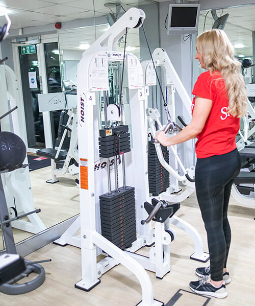 woman using cable machine in gym