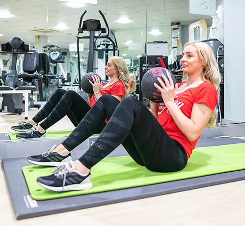 woman doing sit-ups in the gym