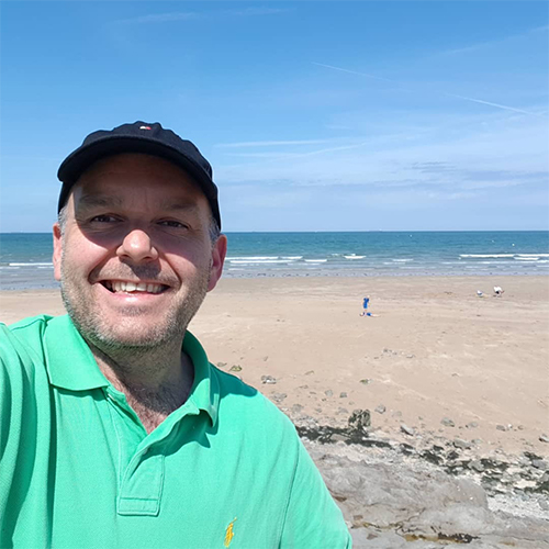 Andrew smiling in front of beach-summer activity ideas-slimming world blog