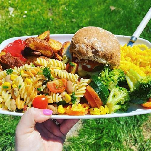 Pasta salad with burger, potato wedges, broccoli and savoury rice