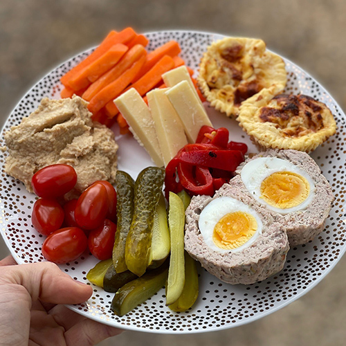 Carrots, gherkins, plum tomatoes, red peppers, cheese sticks, ham and pineapple muffins, scotch eggs and hummus on plate