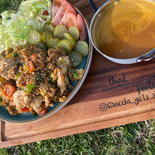 Chicken fried rice with curry sauce on chopping board outside